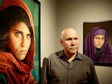 El fotógrafo, posando con los retratos de la niña afgana más famosa del mundo, y tres instantáneas tomadas por él.