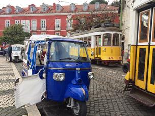 Un tuktuk seguido por uno de los tranvías de Lisboa.